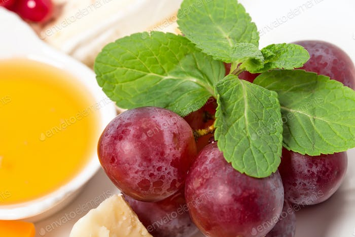 Cheese platter with red grapes and honey.