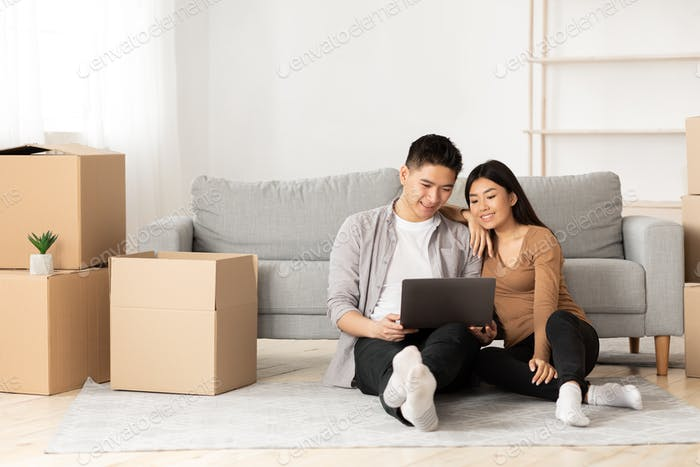 Young asian couple using laptop sitting on floor