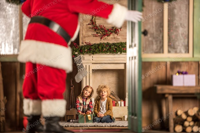 Children sitting near fireplace and waiting for Santa Claus