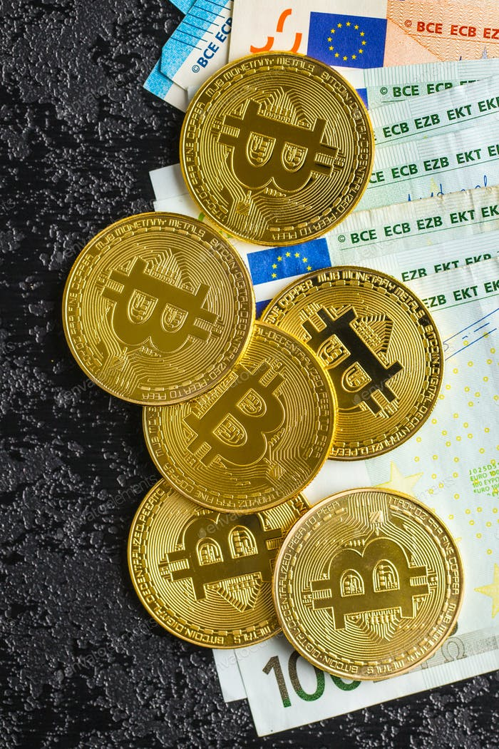 Golden bitcoins and euro banknotes.