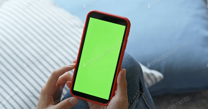 Woman hold with mobile phone with green screen