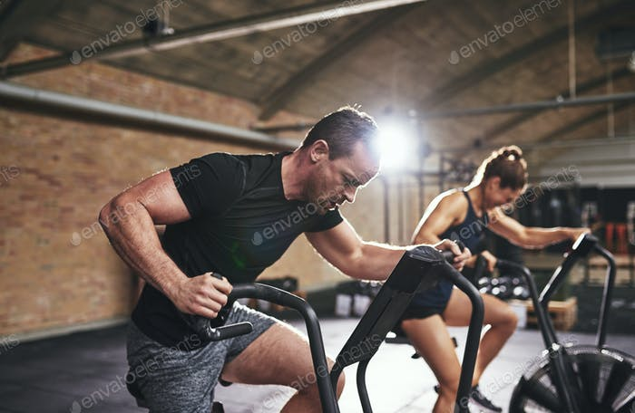 Man and woman training with gym equipment