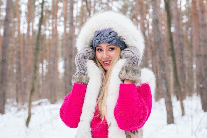 Winter-, Beauty- und Modekonzept - Porträt der blonden jungen Frau im Pelzmantel bei verschneiten Natur