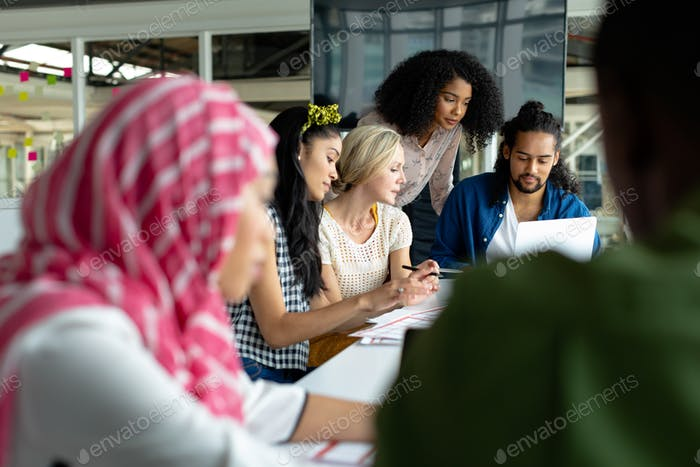 Diverse business people working together on laptop at conference room