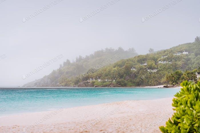 Tropical rain covered Anse Intendance beach on Mahe island in Seychelles