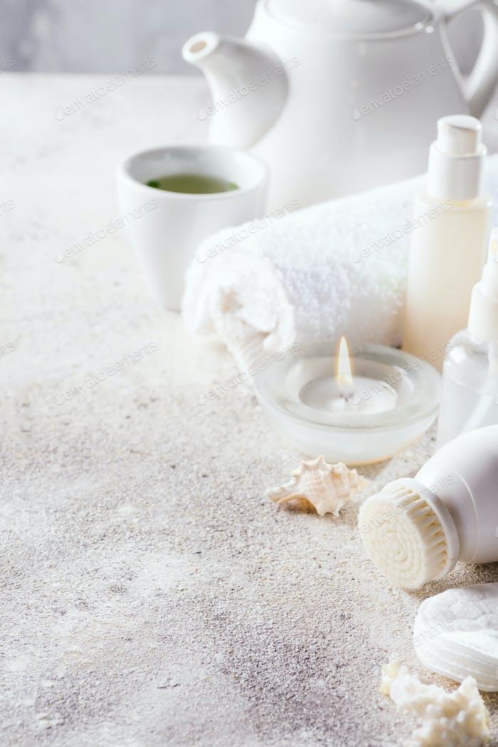 Weißer Kosmetik-Gesichtspflege-Rahmen mit Tee-Set auf hellem Steinhintergrund. Sauberes Beauty-Konzept
