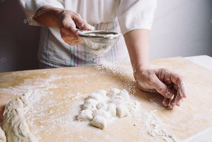 Two hands making dough for meat dumplings.