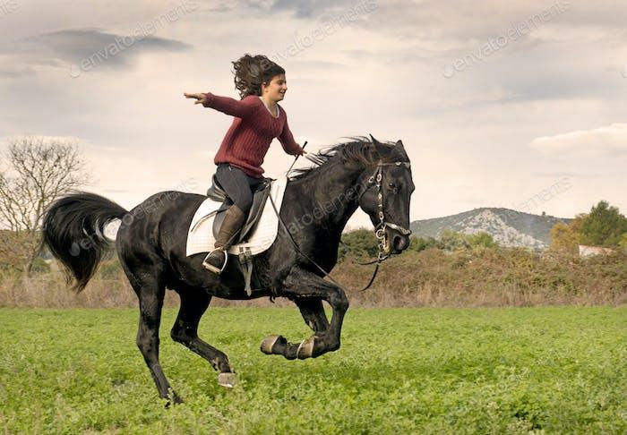 riding girl and black stallion