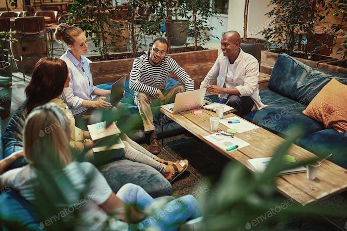 Разнообразные молодые бизнесмены, собравшись за журнальным столиком на работе