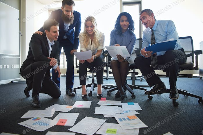 Businesspeople brainstorming with paperwork laid out on an office floor