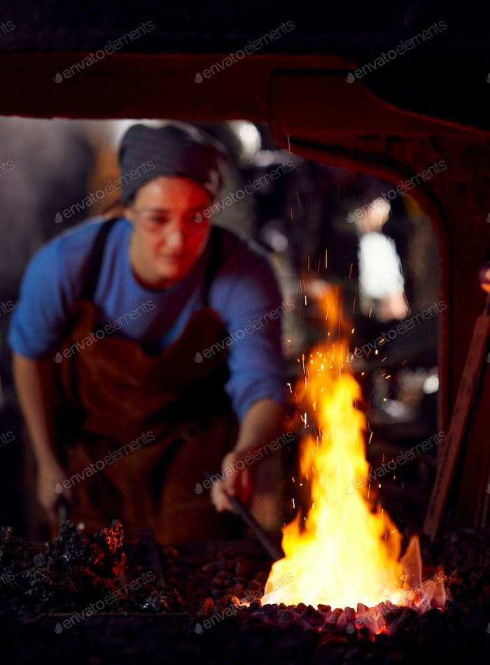 Female Blacksmith Heating Metalwork In Flames Of Forge
