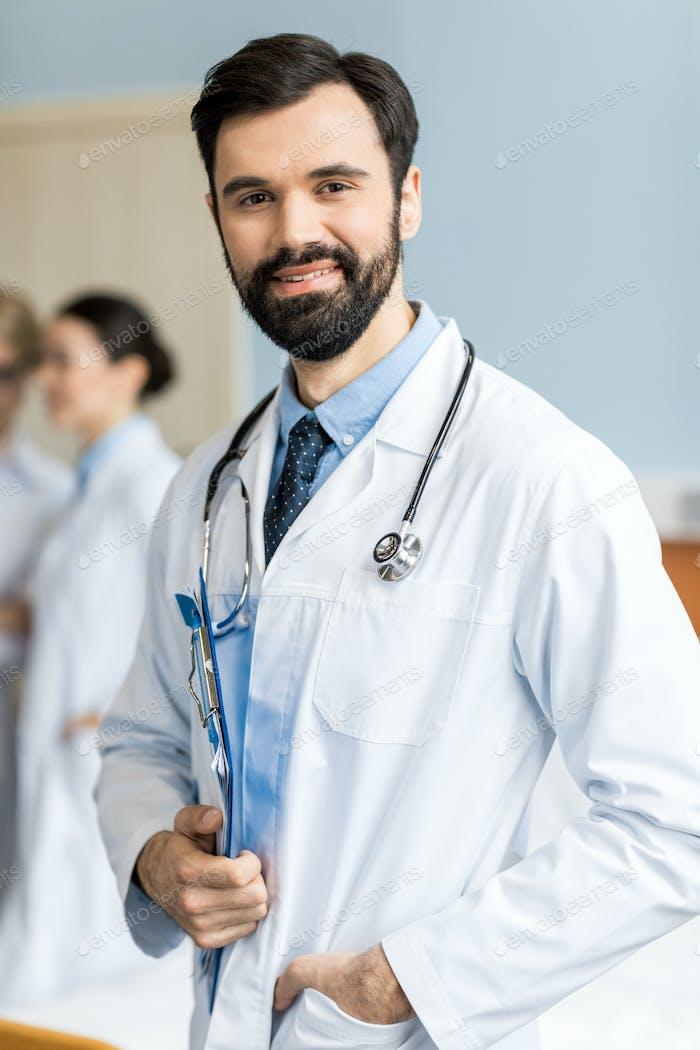 Porträt von lächelnden Arzt mit Arzt Stethoskop und Ordner in der Klinik