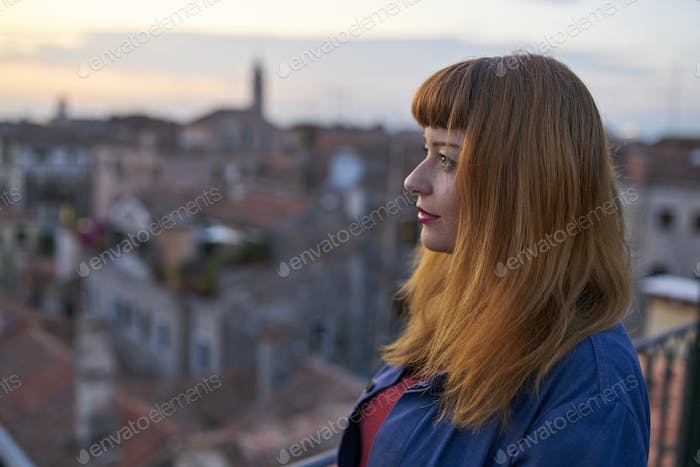 Caucasian redhead woman with denim dress overlooking rooftops in Venice
