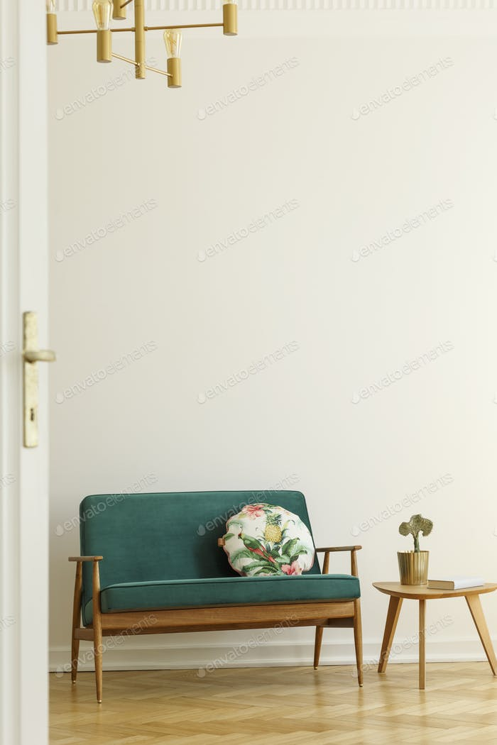 Floral pattern pillow on a retro style, green sofa and a wooden
