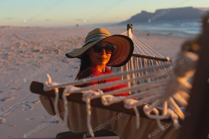 Retrato de la mujer de raza mixta feliz en vacaciones en la playa mirando a la cámara sentada en la hamaca al atardecer