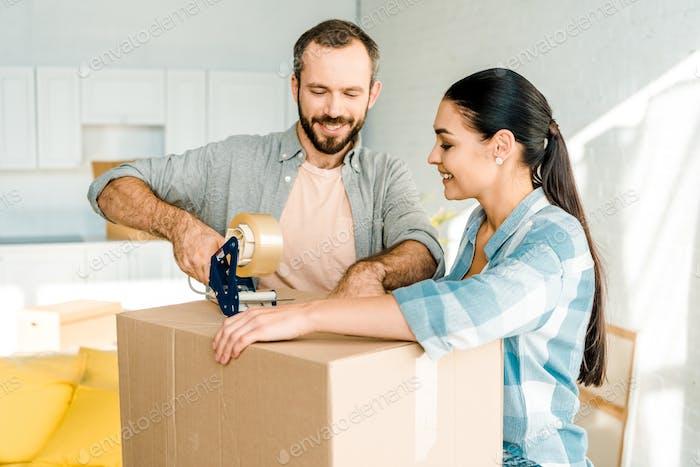 gut aussehender Mann und Frau, die Pappschachtel mit Klebeband verpacken, bewegliches Konzept
