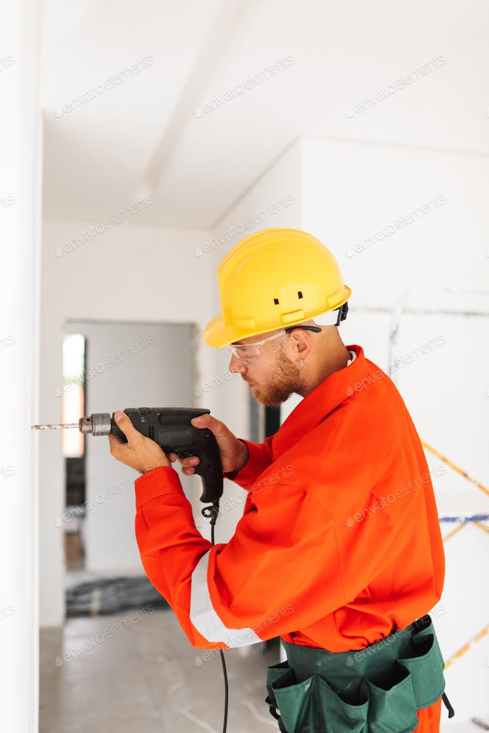 Young builder in orange work clothes and yellow hardhat using el