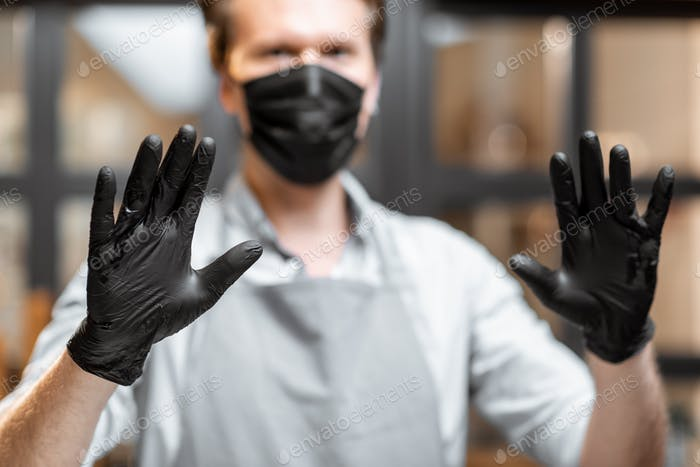 Salesman in protective wear in the cafe during a pandemic
