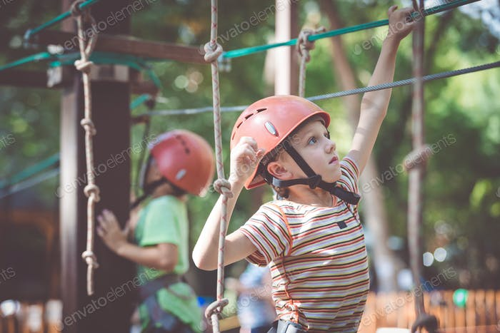 little boy make climbing in the adventure park.