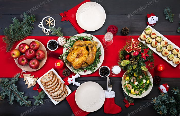 The Christmas table is served with a turkey, decorated with bright tinsel and candles.