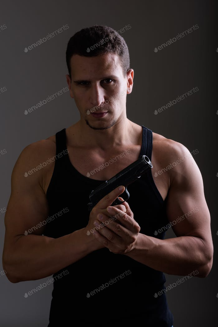 Studio shot of young muscular Persian man holding gun and lookin