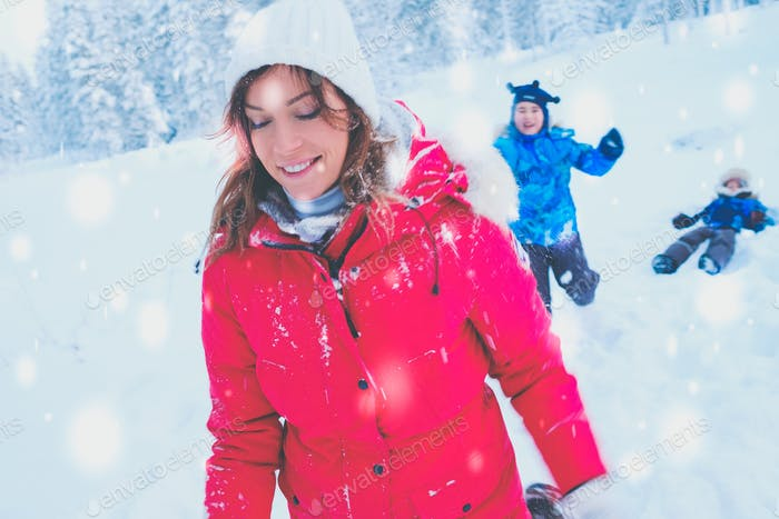 Happy mother with her children playing in a snow