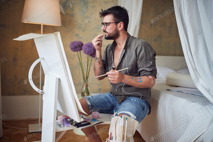 Man artist painting with oil on canvas.