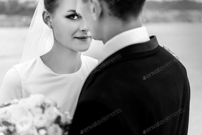 glückliche Braut und stilvollen Bräutigam am Sandstrand Küste umarmt und lächelnd, Luxus-Hochzeit, bw