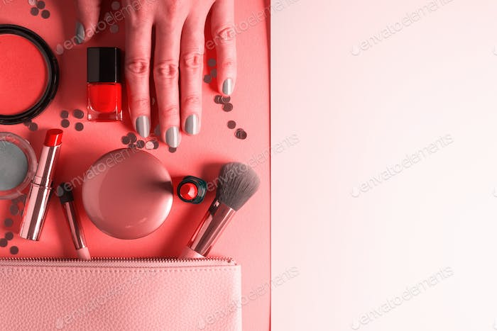 Make up items on pink coral and hand with manicure