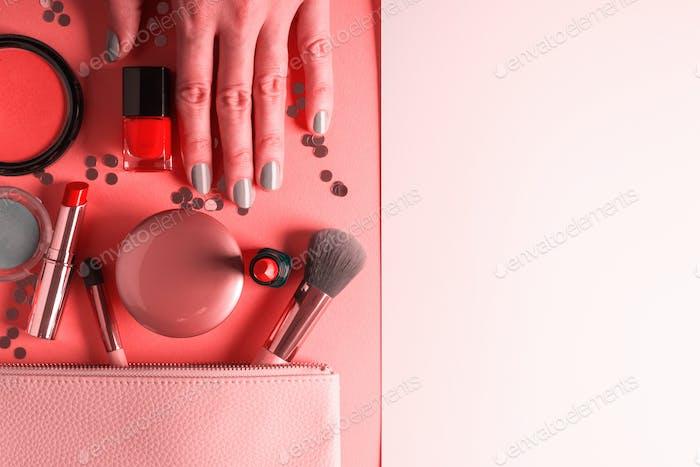 Make-up-Artikel auf rosa Koralle und Hand mit Maniküre