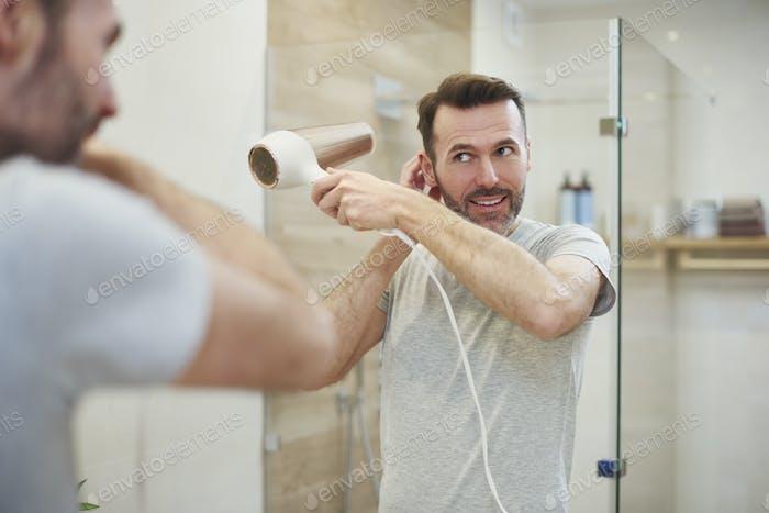 Smiling man using hairdryer in bathroom