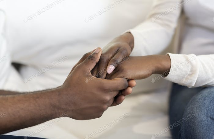 African American Couple Holding Hands While Sitting On Couch