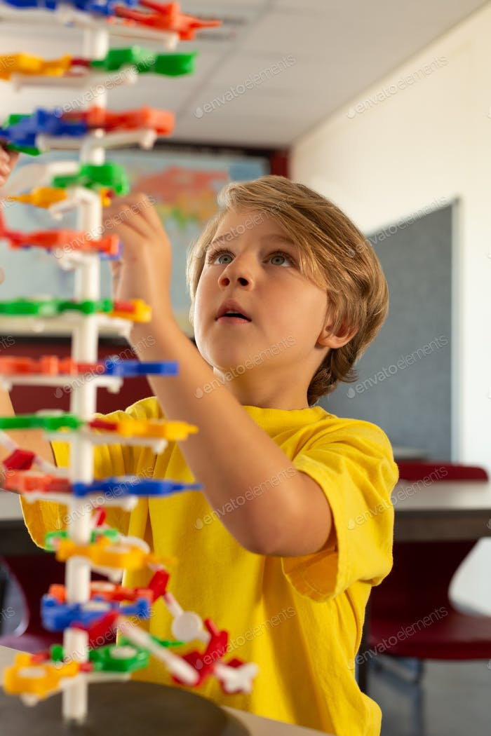Front view of Caucasian boy learning science model in classroom at elementary school