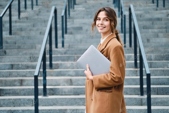 Young pretty casual businesswoman in coat with laptop happily looking in camera outdoor
