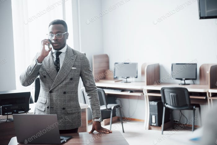 heerful african businessman standing in front of colleague