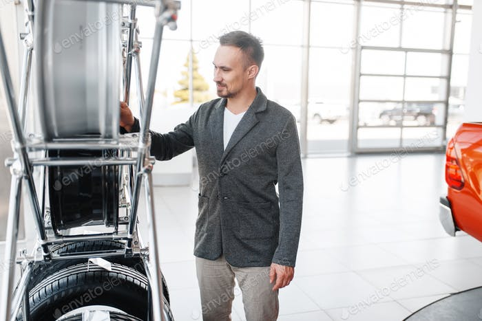 Man choosing wheels for new car in showroom