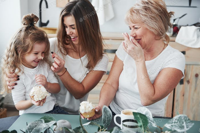 Nose is in the cake. Mother, grandmother and daughter having good time in the kitchen