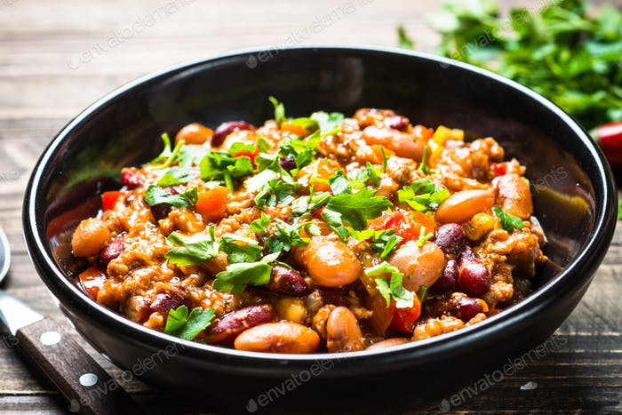 Chili con carne from meat and vegetables on wooden table top view