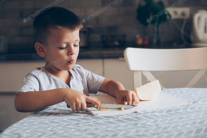 Cute boy 4-5 years old with knife cutting a cheese on the cutting board on the table in the kitchen