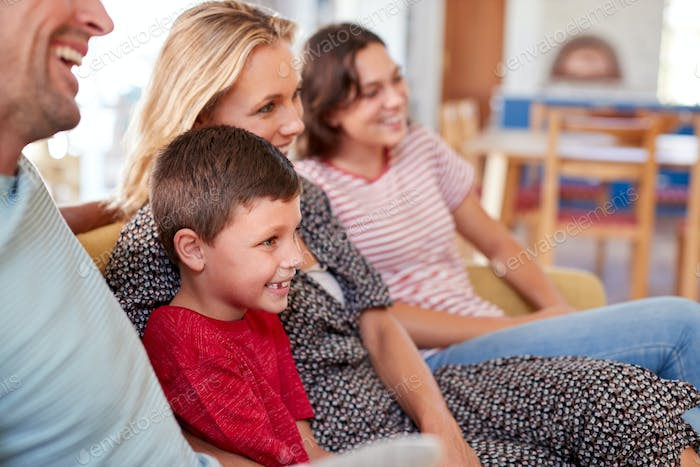 Multi-Generation Family Sitting On Sofa At Home Watching Movie Together
