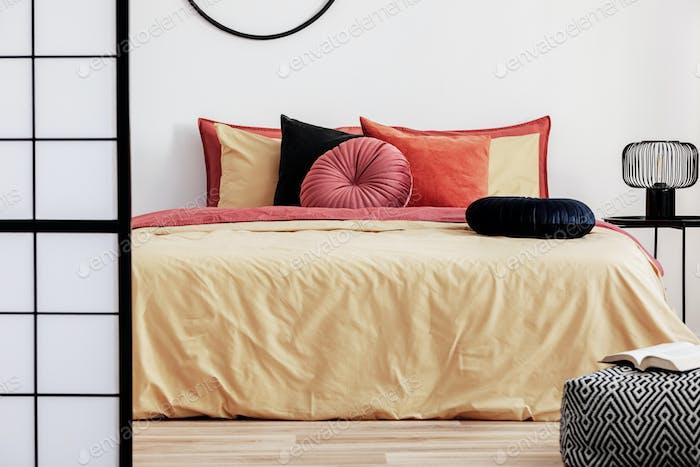 Schwarzes rundes Samtkissen auf gelber Bettdecke im trendigen Schlafzimmer mit King-Size-Bett