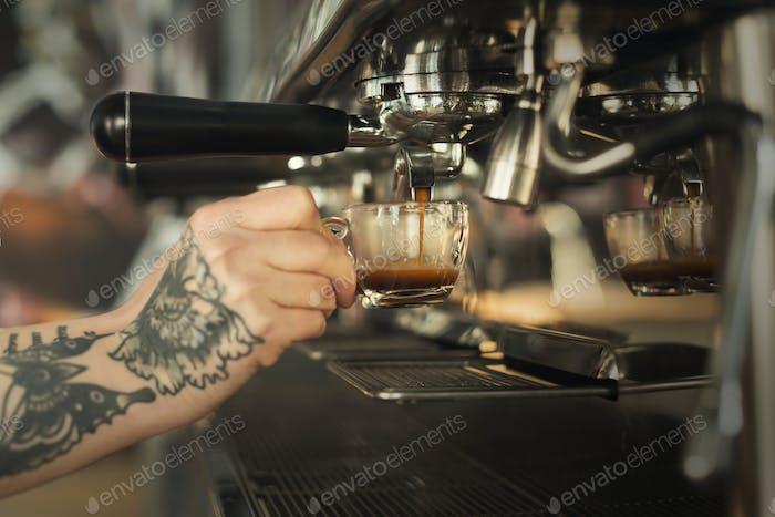 Closeup of female hand brewing espresso in professional coffee machine