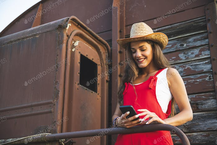 Beautiful Young girl Smiling and Using Smartphone for Texting