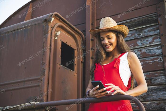 Schönes junges Mädchen lächelnd und mit Smartphone für SMS