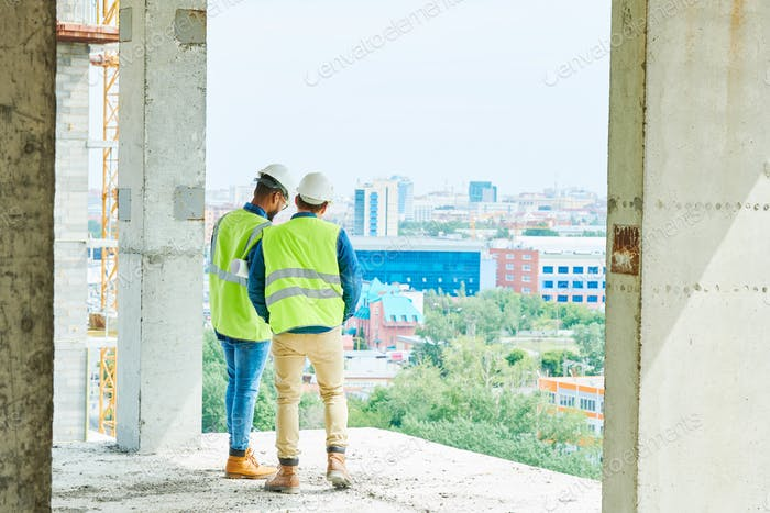 Men in hardhats at construction site of apartment building
