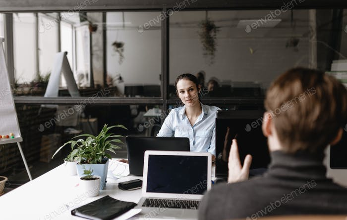 Young woman and guy dressed in office style clothes are working sitting at desks in the light modern