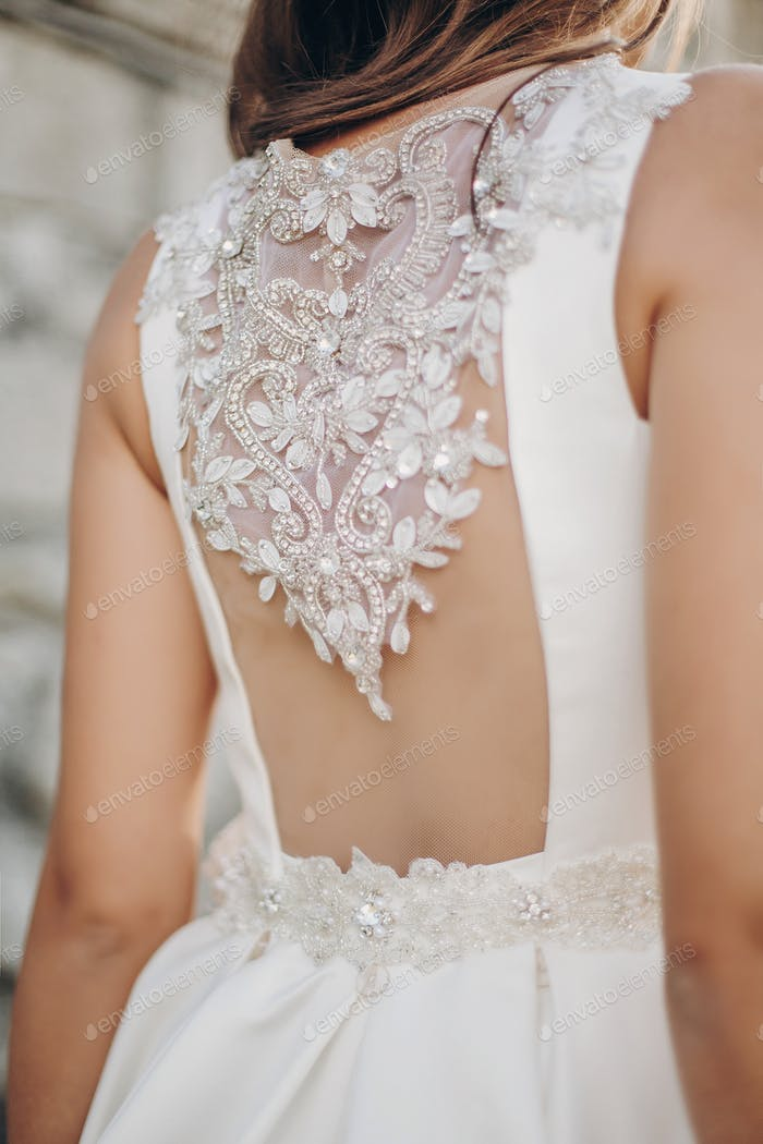 Back of stylish wedding bride in luxury white dress with stones and gems