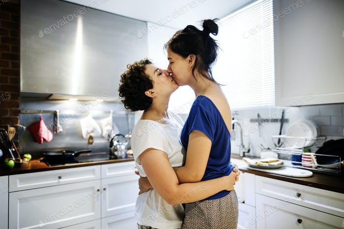 Lesbian couple kissing in the kitchen