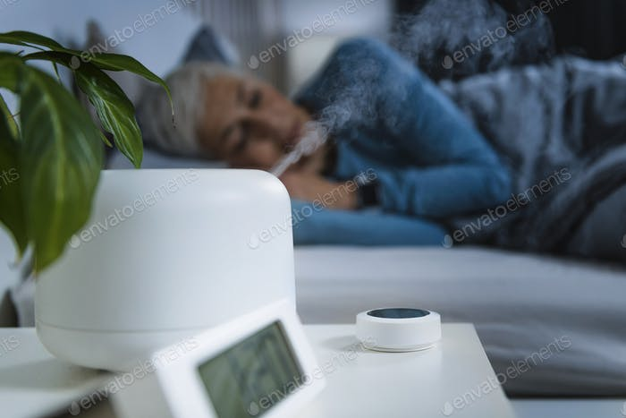 Air Humidifier Increasing the Humidity in a Bedroom. Beautiful Mature Woman Sleeping in Bed.