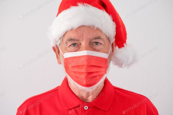 Senior serious man dressed in red as santa claus wearing a red surgical mask due to coronavirus